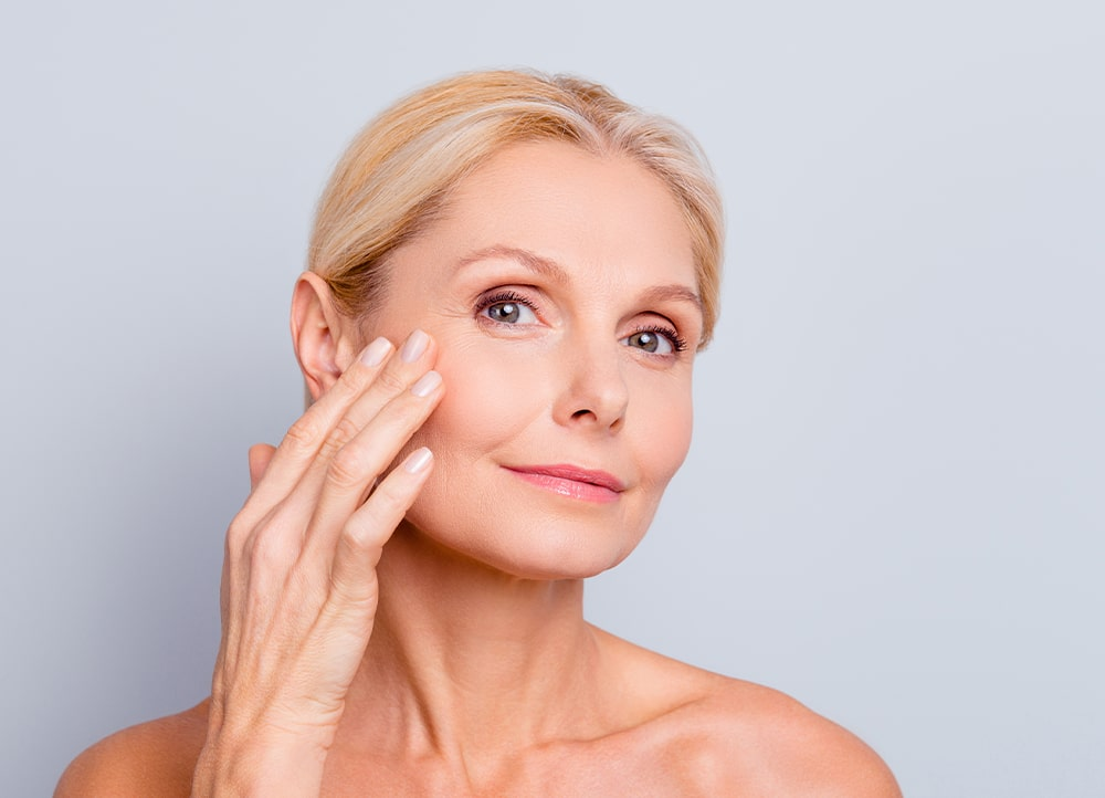 an older woman complete a skin care treatment for aging