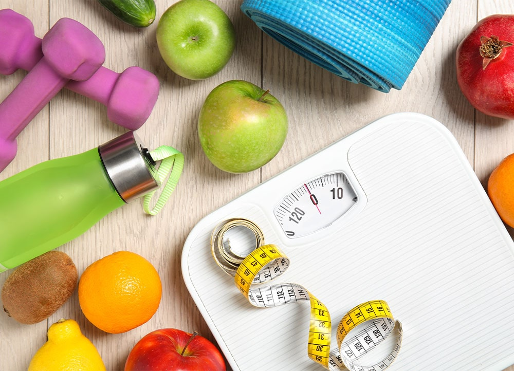 healthy foods, work out equipment, and scale with measuring tape