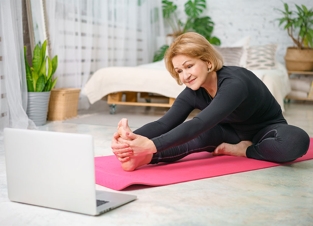 older woman stretching on yoga mat before exercise